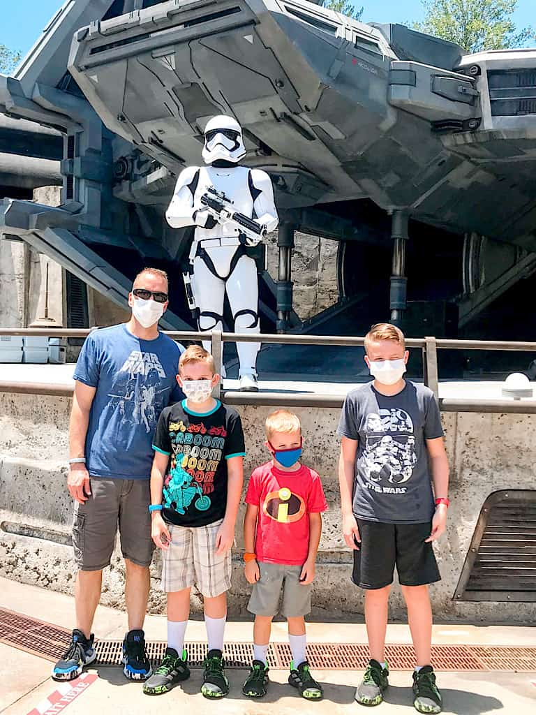 A dad and three boys wearing face masks at Disney World in front of a Storm Trooper.