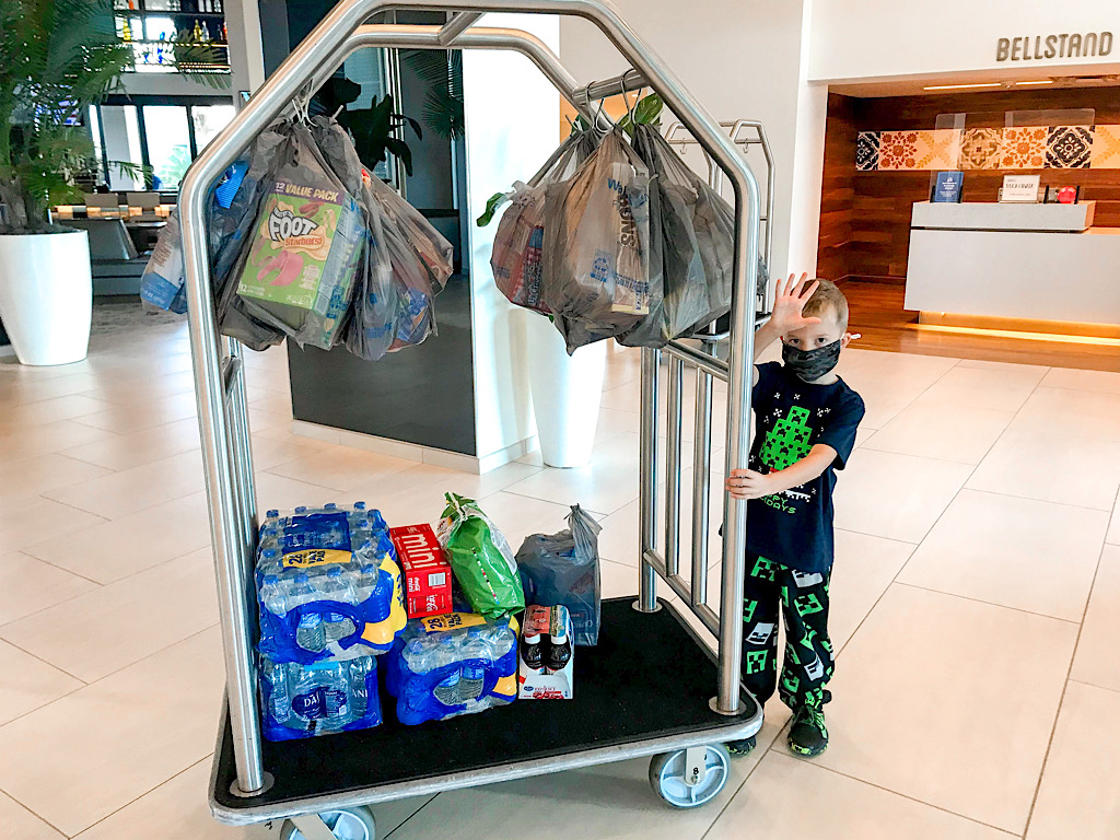 A boy with a luggage cart full of groceries at a Disney resort hotel.