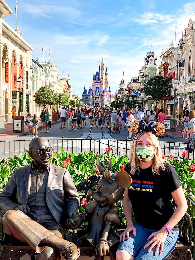 A lady sitting next to a statue of Walt Disney on Main Street at Magic Kingdom