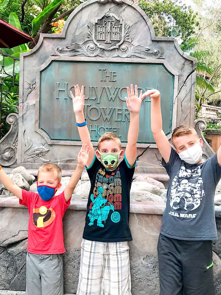 Three boys with their arms up in front of a sign for the Tower of Terror at Hollywood Studios.