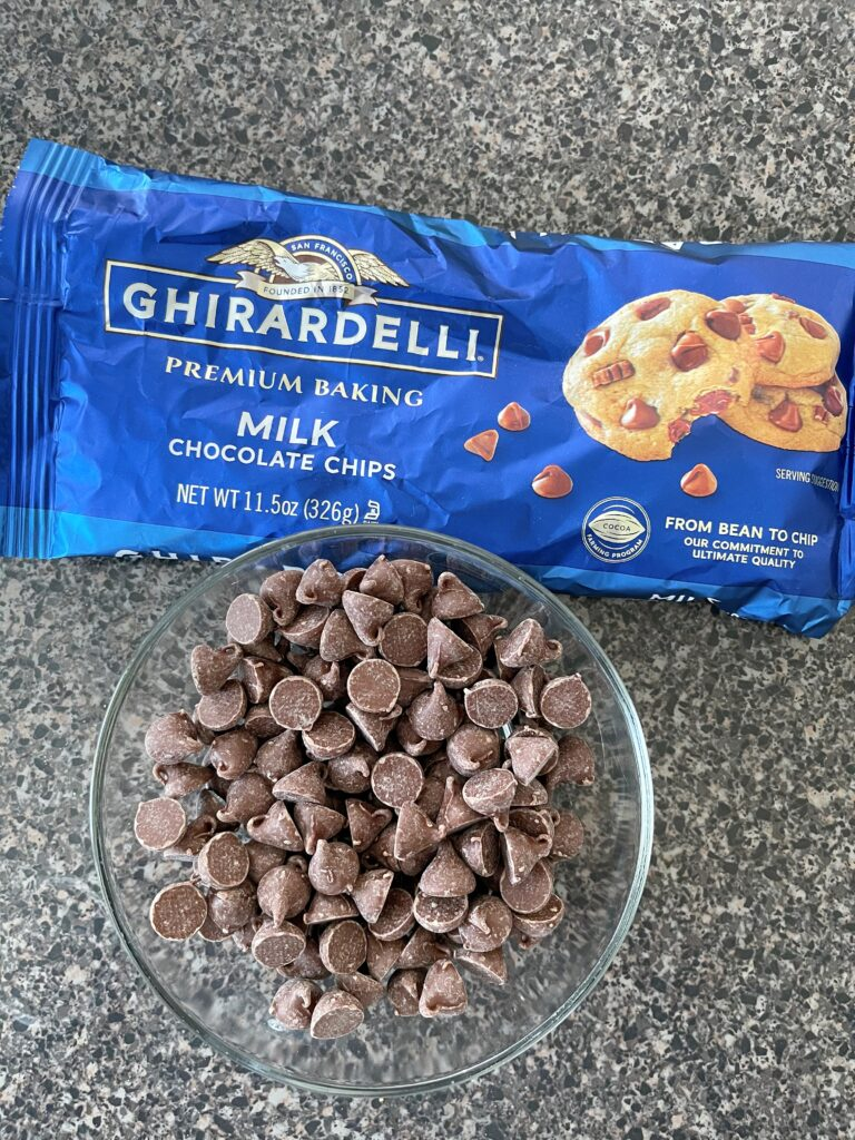 A bag of Ghirardelli chocolate chips and a bowl of chocolate chips.