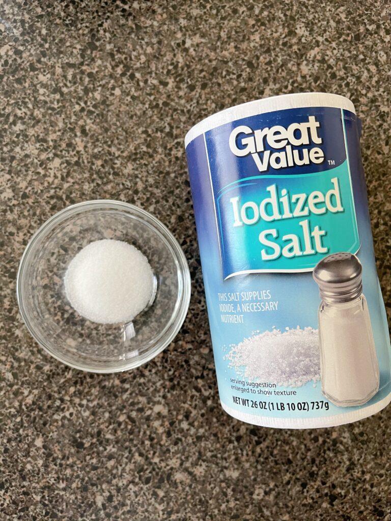 A small bowl of salt next to a cylinder of salt.