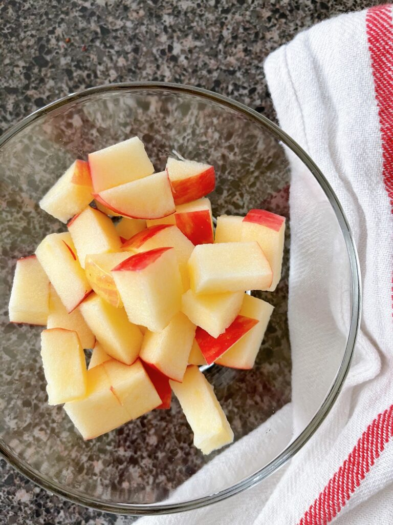 A bowl with a cut up Honeycrisp apple.