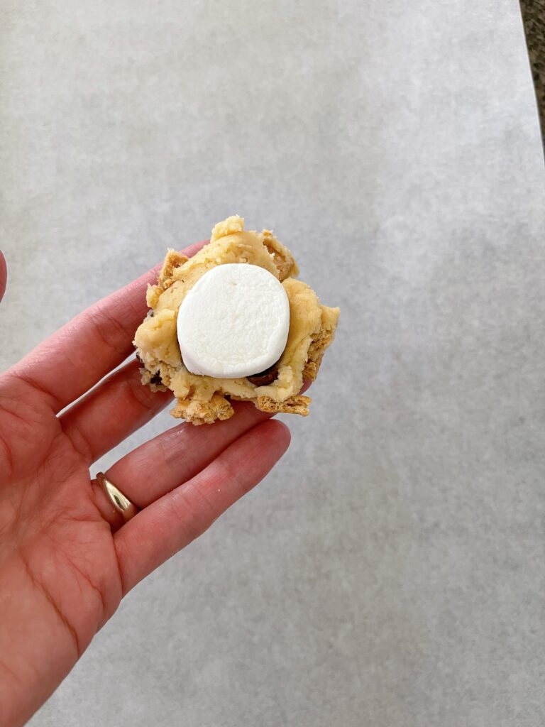 Cookie dough being wrapped around a jumbo marshmallow.