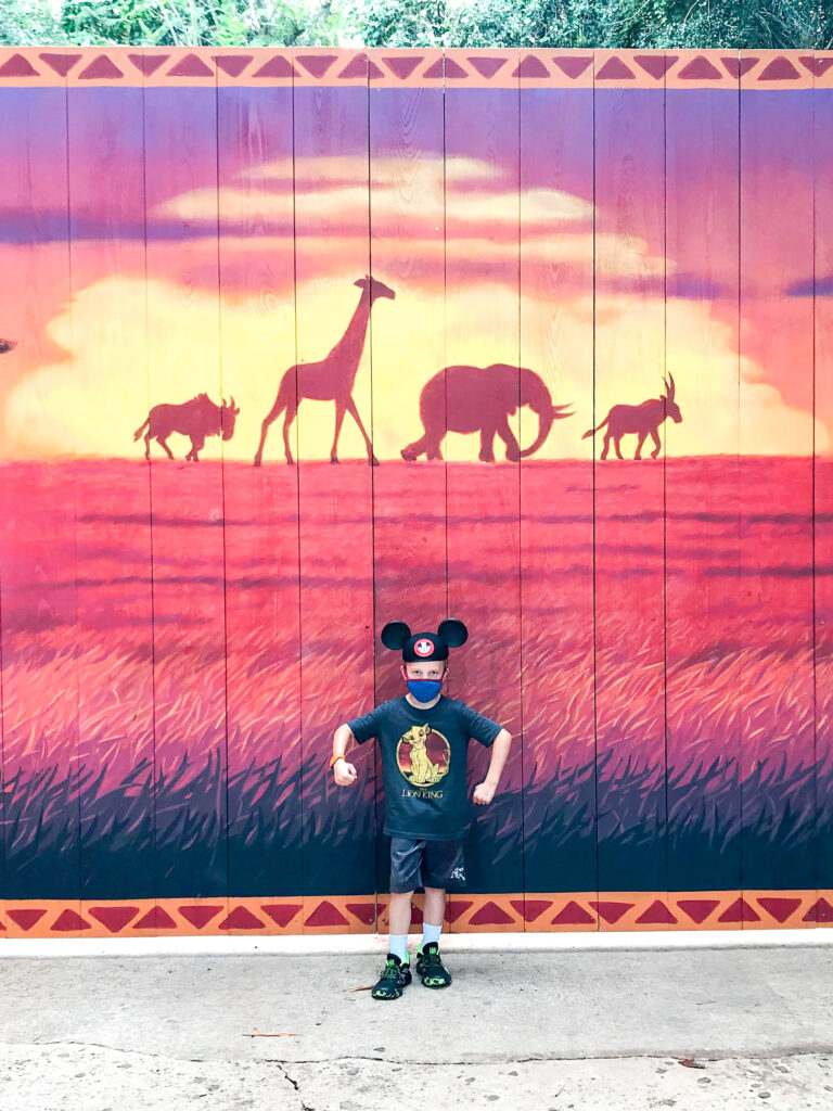 A boy in Mickey ears in front of a Lion King sign at Disney's Animal Kingdom.
