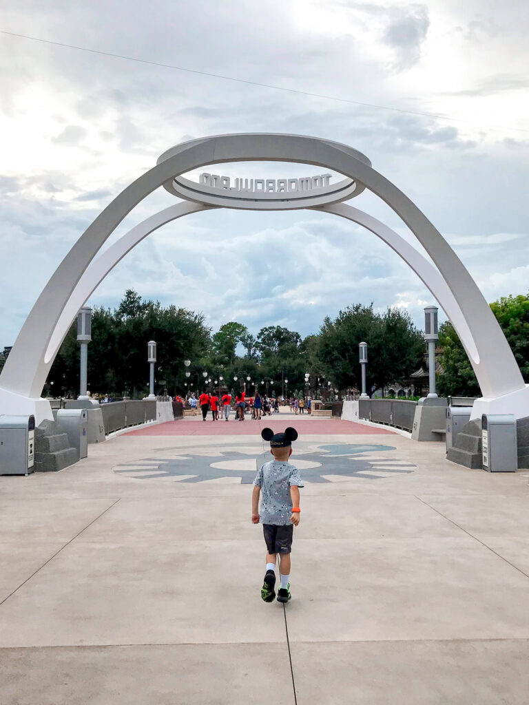 A boy in a Mickey hat in front of Tomorrowland.
