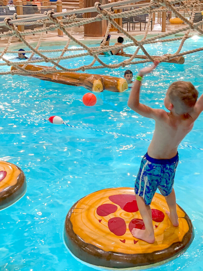 A boy climbing on lilly pads at Great Wolf Lodge.