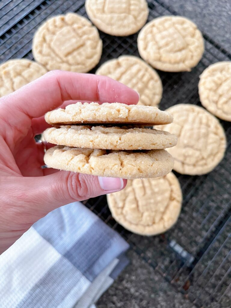 A hand holding three peanut butter cookies.