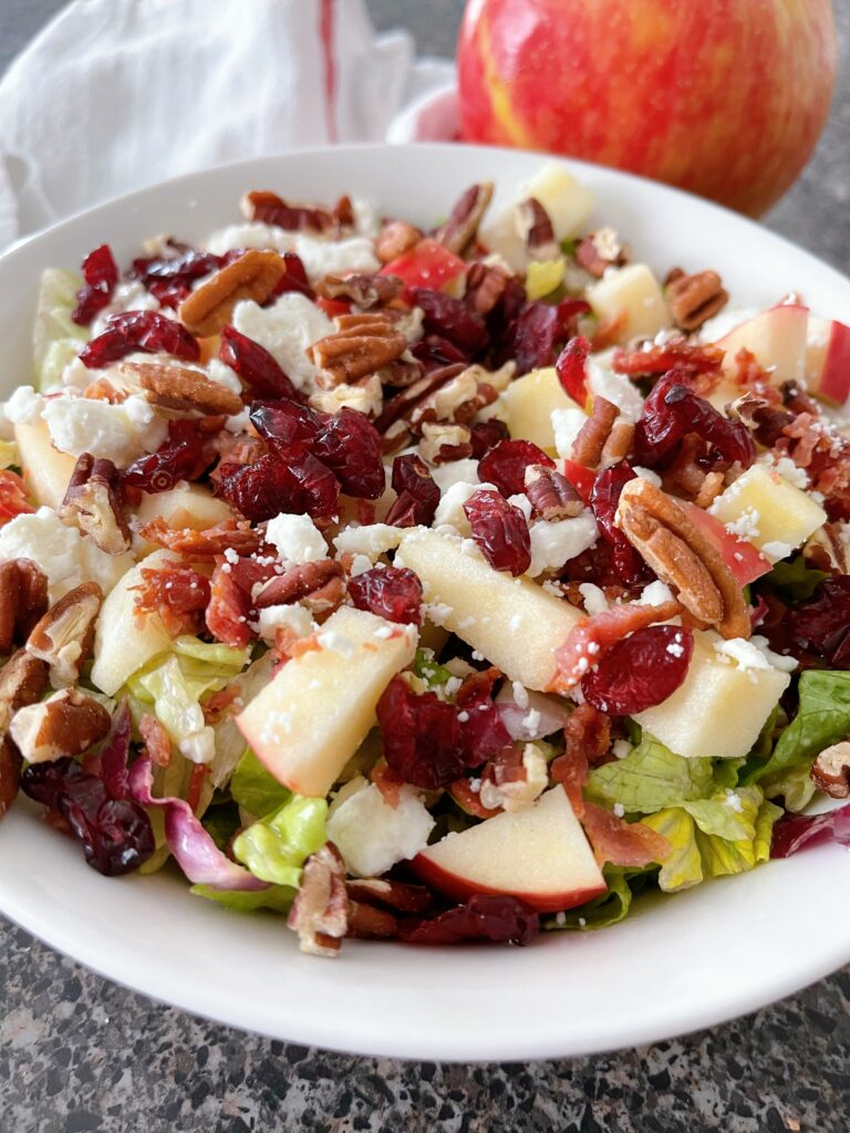 A salad with apples, cranberries, bacon, pecans, and feta cheese.