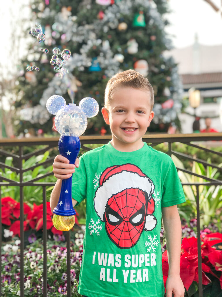 A boy at Disneyland holding a Mickey Mouse bubble wand.