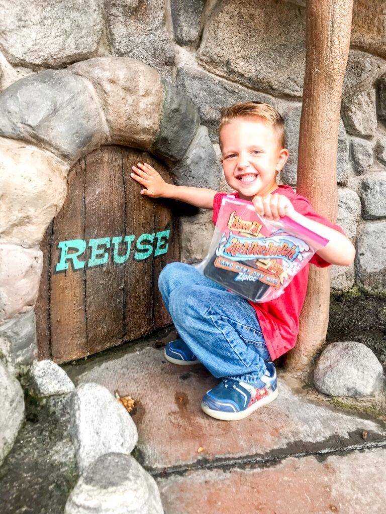 A boy outside Splash Mountain holding a Ziploc Bag.