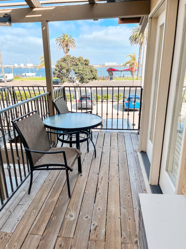 Deck with two chairs and a table with a view of San Diego Bay.