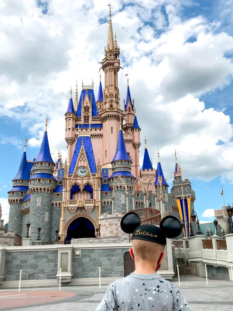 A boy in Mickey Ears in front of Cinderella Castle.