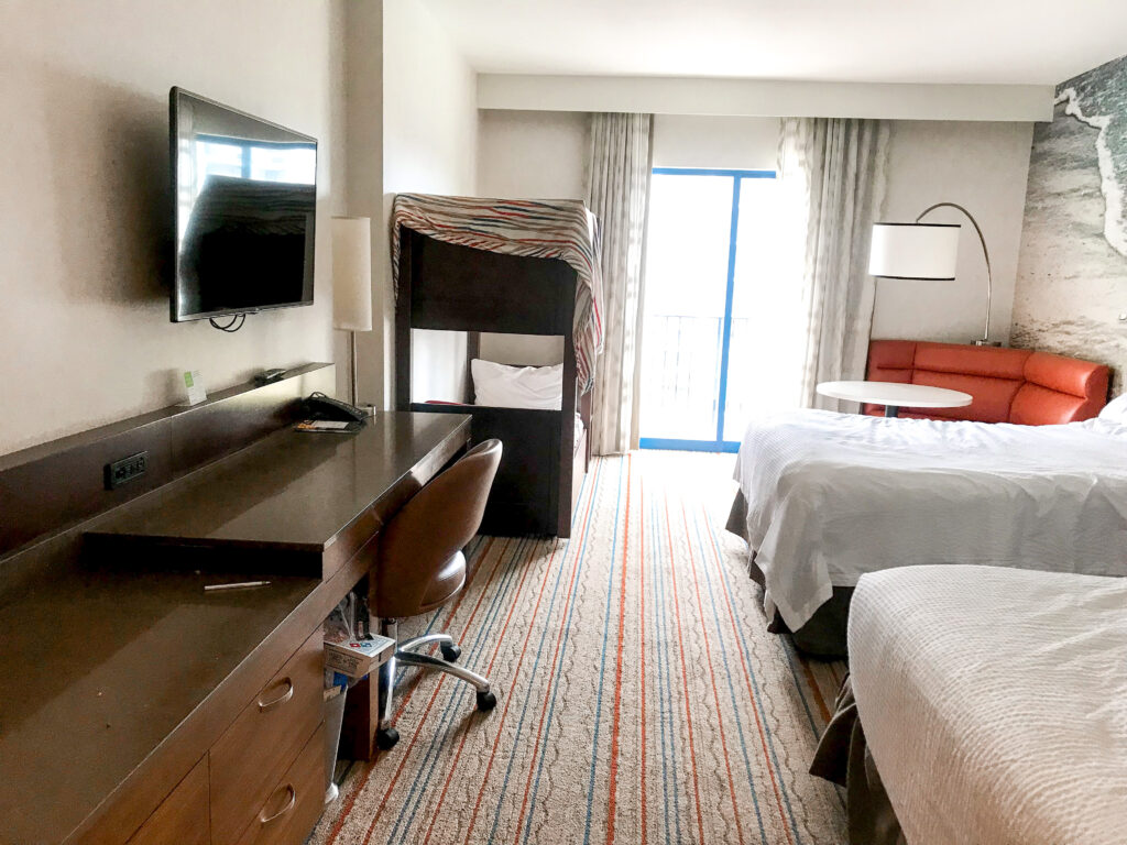 Two queen beds, table, bunk beds, desk, television in a guest room at Courtyard Anaheim Theme Park Entrance.