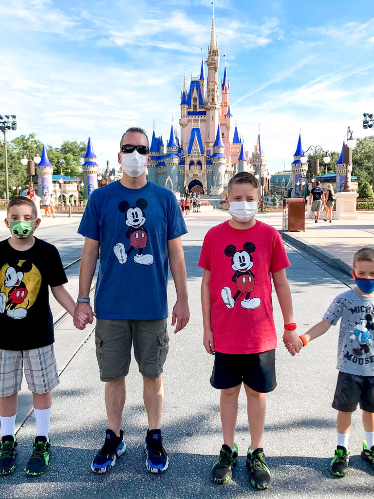 4 people in front of Cinderella Castle in Mickey Mouse shirts.