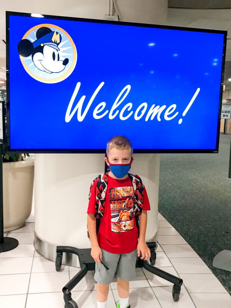 A boy in front of a Disney Welcome sign.