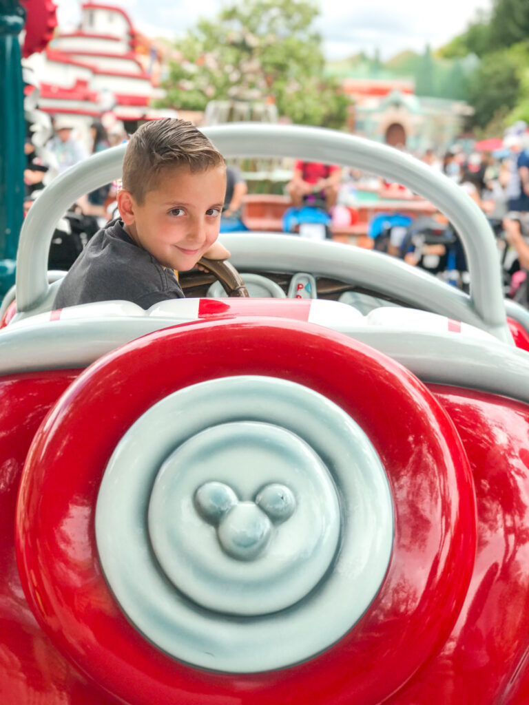 A boy in a Mickey Mouse car in Toon Town at Disneyland.