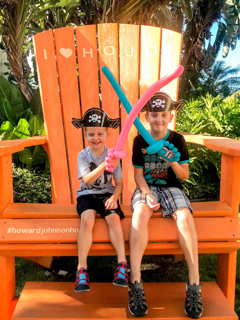 Two kids on a giant orange chair at Howard Johnson Anaheim.
