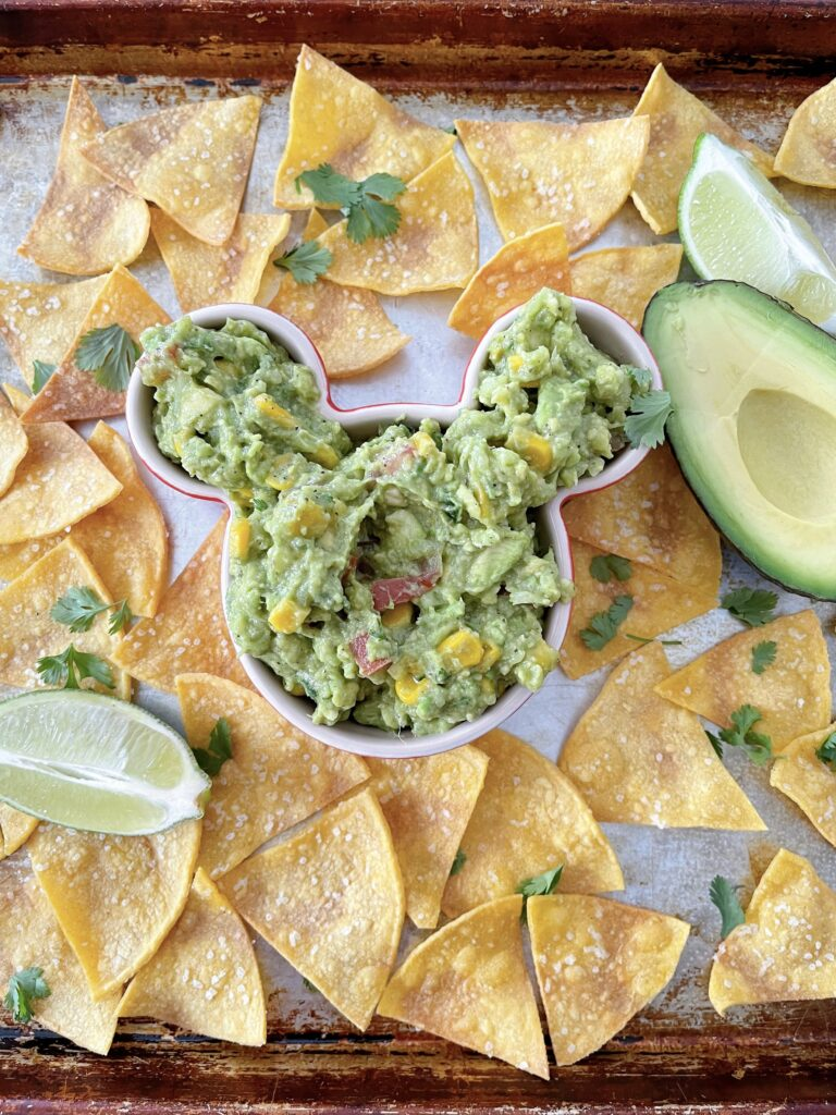 A Mickey Mouse shaped bowl of chunky guacamole.