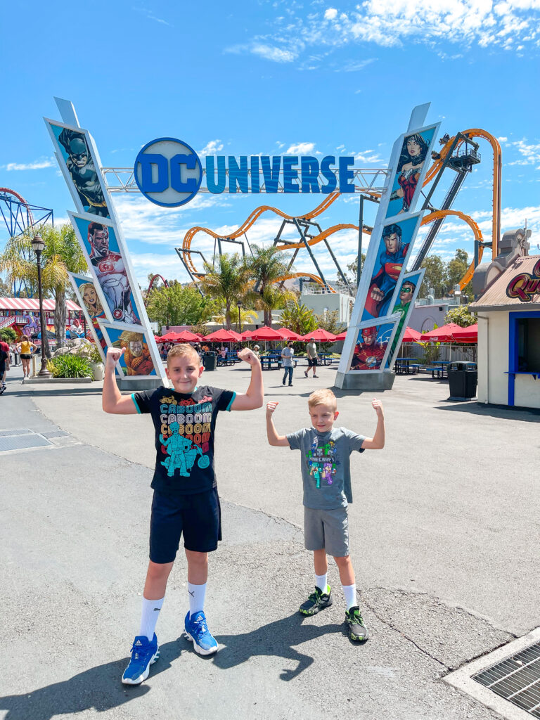 Two kids in front of a DC Universe sign at Six Flags Discovery Kingdom.