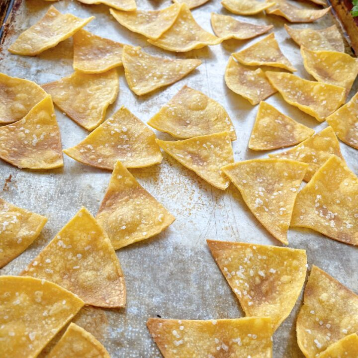 Baked tortilla chips on a pan.