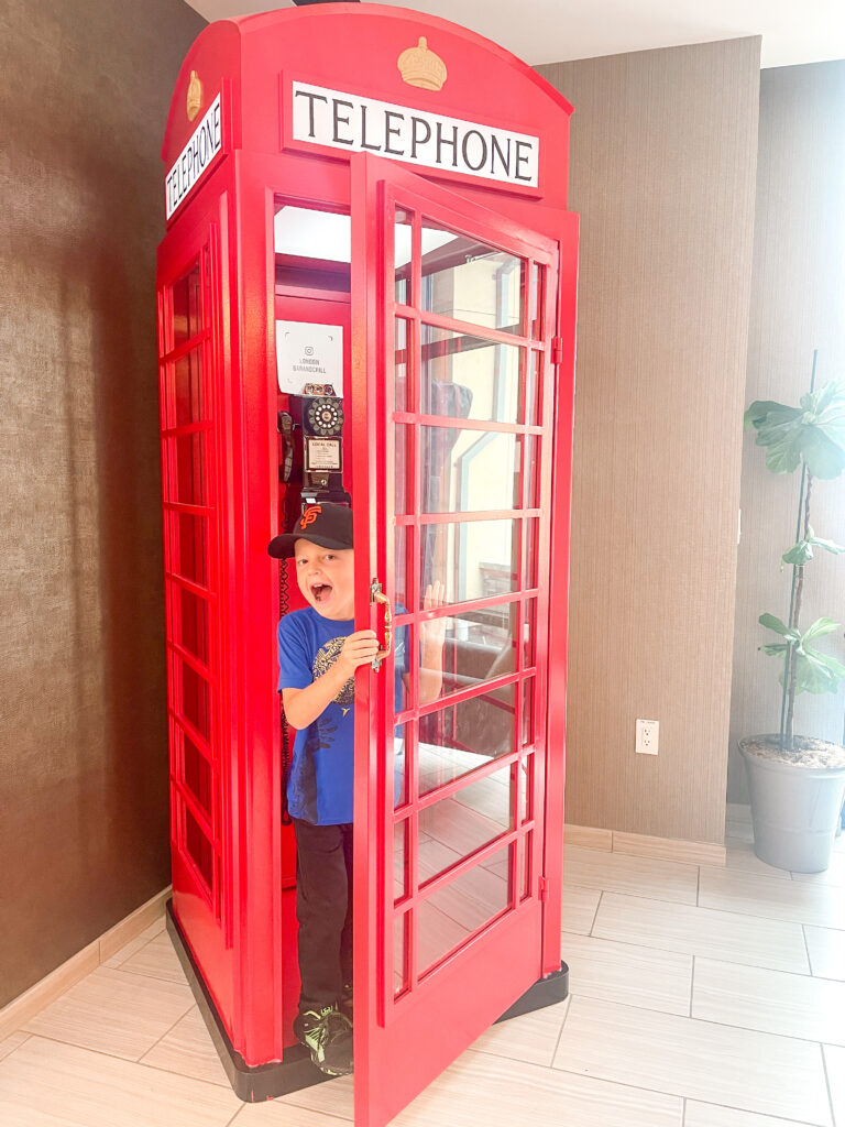 A boy in a red phone booth in San Francisco, California.