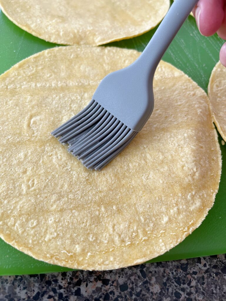 A brush applying oil to the top of a corn tortilla.
