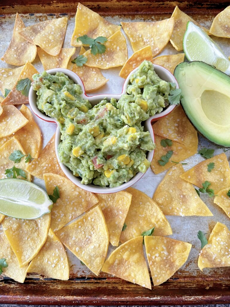 Chunky guacamole in a mickey mouse shaped bowl surrounded by tortilla chips.
