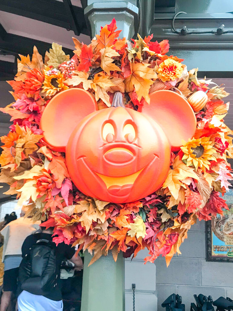 A Mickey Mouse shaped pumpkin in the center of a wreath.