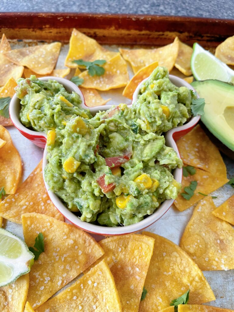 A bowl of guacamole and tortilla chips.