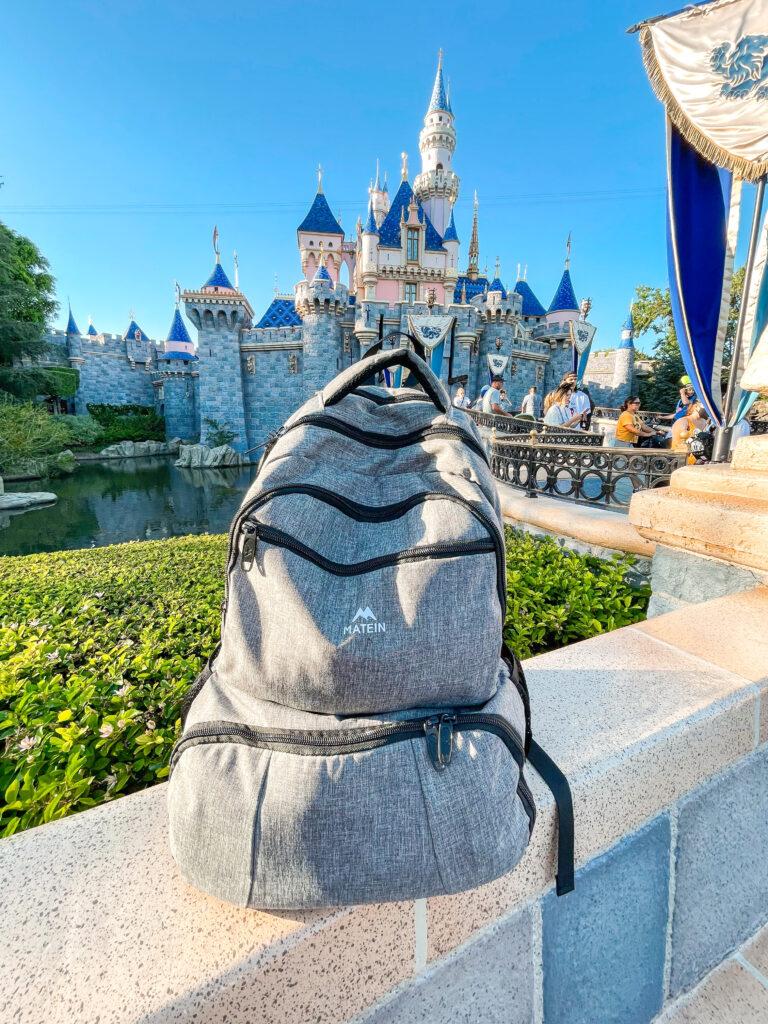 A backpack in front of Cinderella Castle at Disneyland.