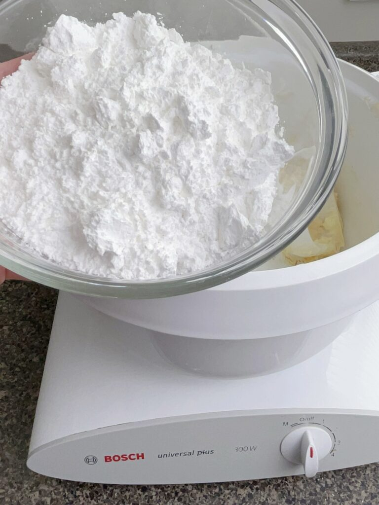 Powdered sugar being added to a mixer with butter to make frosting for cream cheese sugar cookie bars.