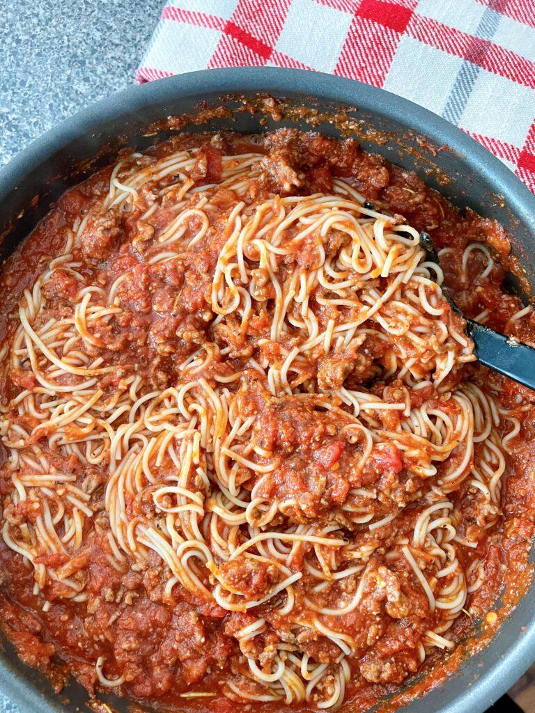 A pan of spaghetti and spaghetti sauce.