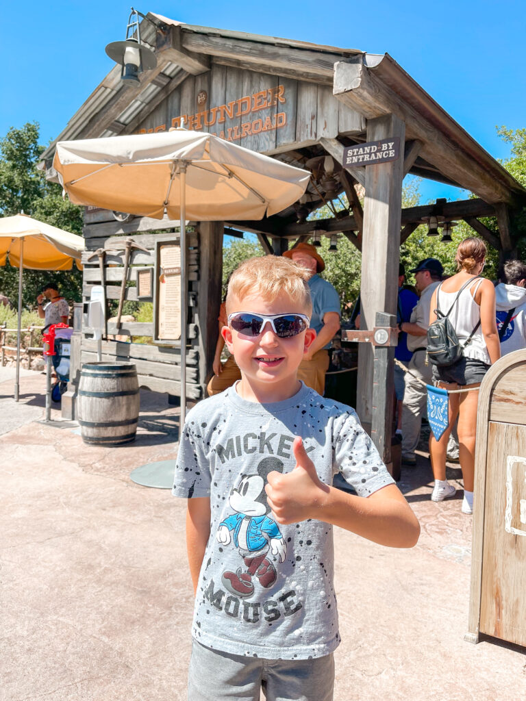 A boy in Storm Trooper sunglasses at Disneyland.