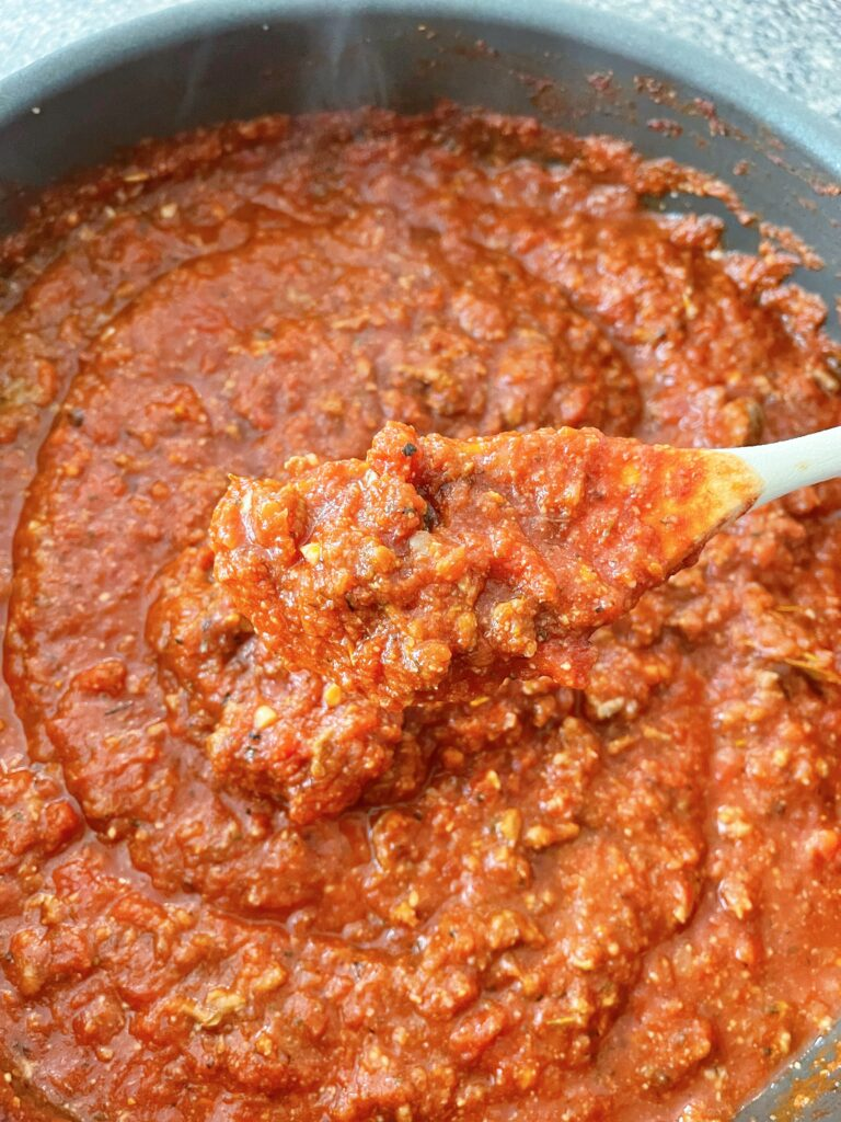 Spaghetti sauce in a pan with a wooden spoon.