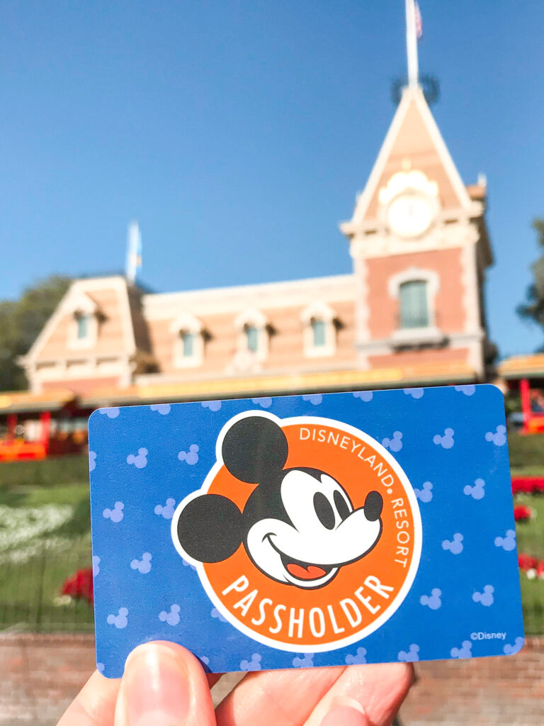 A Disneyland annual pass in front of the Disneyland Railroad.