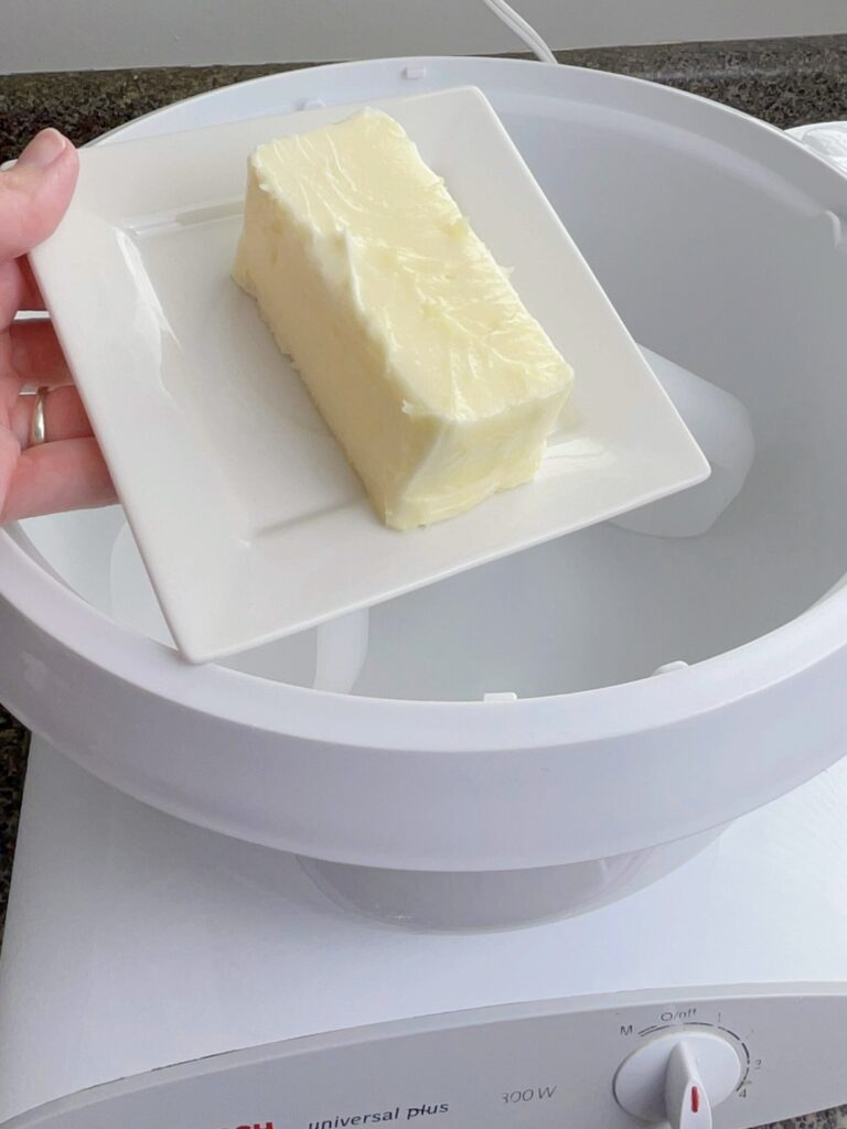 Butter being added to the bowl of a stand mixer to make frosting.