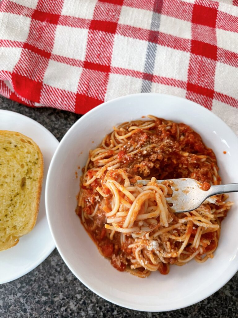 A bowl of spaghetti sauce and a piece of garlic bread.