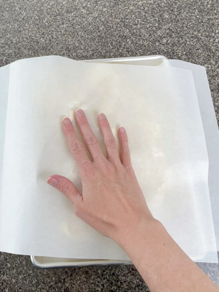 A hand pressing cookie dough on a baking sheet to level it.