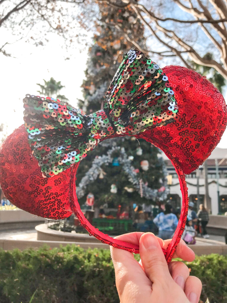 Minnie ears in front of the Christmas tree on Buena Vista Street at Disney California Adventure.