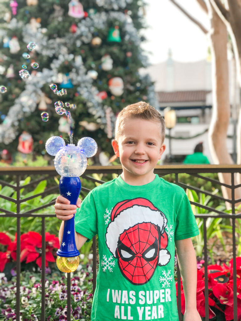 A boy in a Spider-Man Christmas shirt with a Mickey Mouse bubble wand.
