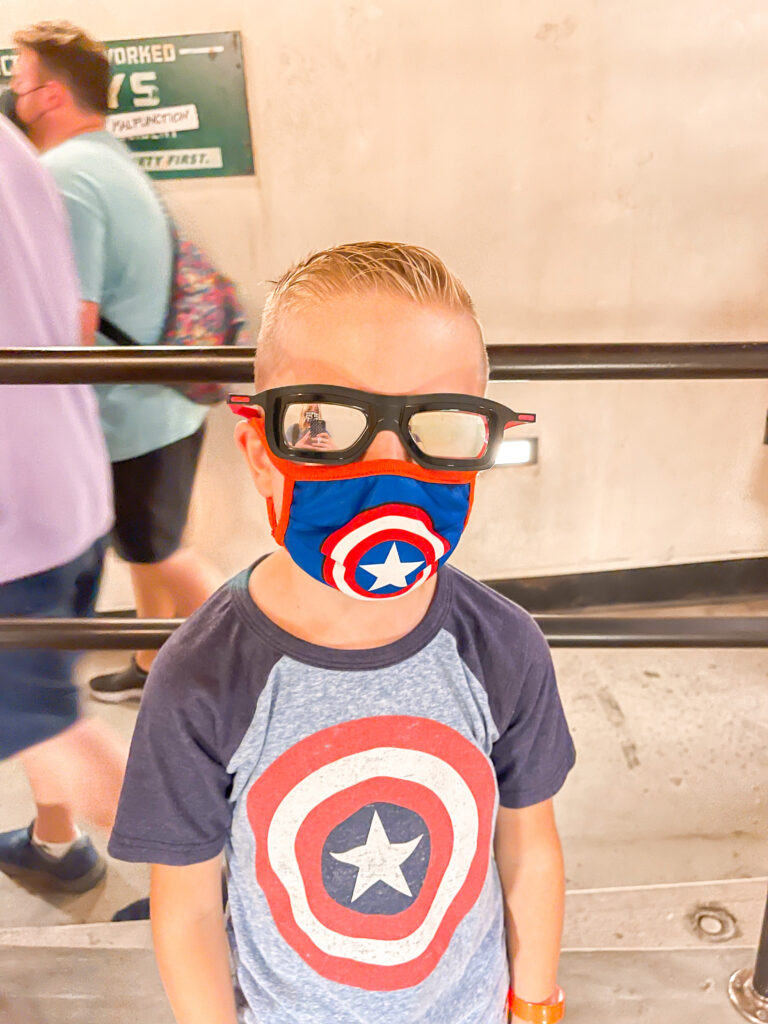 A boy in sunglasses, a Captain America mask and shirt at Web Slingers at Disneyland.