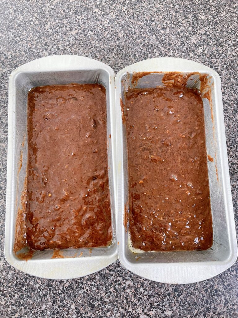 Two loaf pans filled with zucchini bread batter.