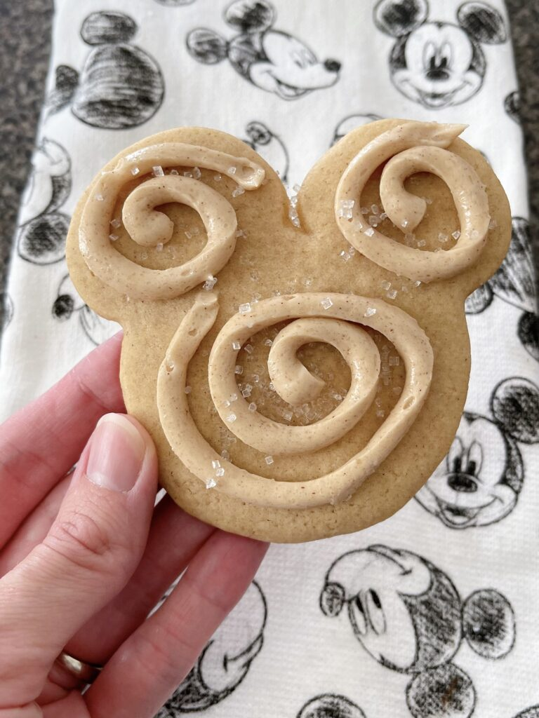 A Mickey Mouse-shaped churro sugar cookie swirled with churro frosting.