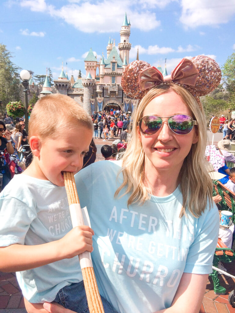A little boy and his mom eating a churro at Disneyland.