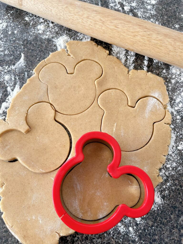 A Mickey mouse cookie cutter with cookie dough.