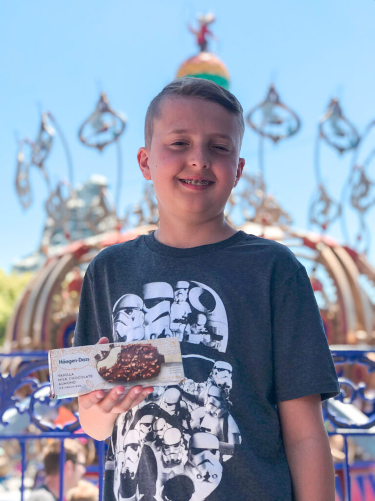 A boy with an ice cream bar at Disneyland.
