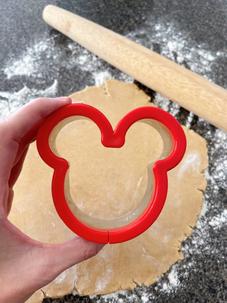 A Mickey Mouse cookie cutter with cookie dough and a rolling pin.