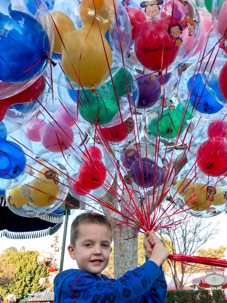 A boy at Disneyland with a bunch of balloons.