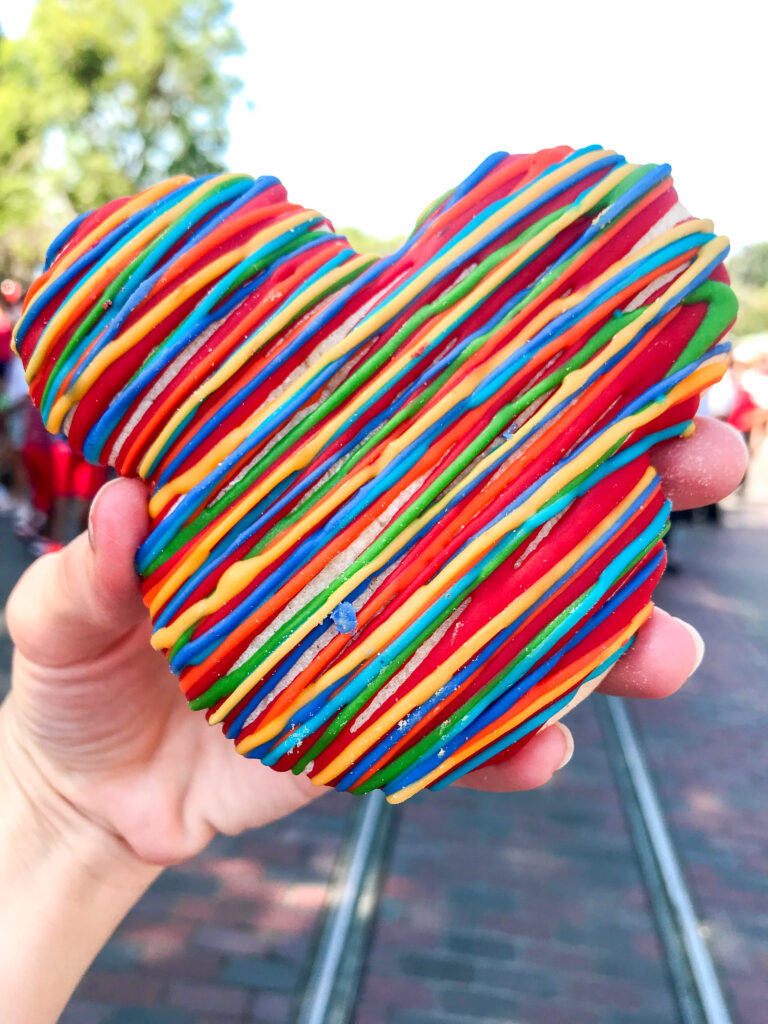 A Mickey Mouse-shaped sugar cookie drizzled with colored candy melts.